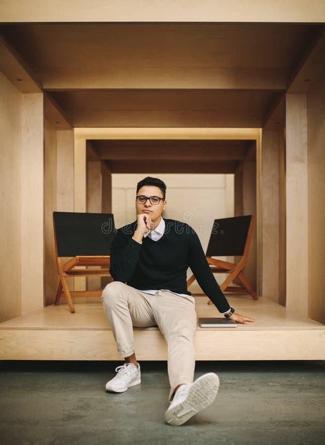 Homem de negócios que senta-se no escritório dentro de um cerco fotografia de stock