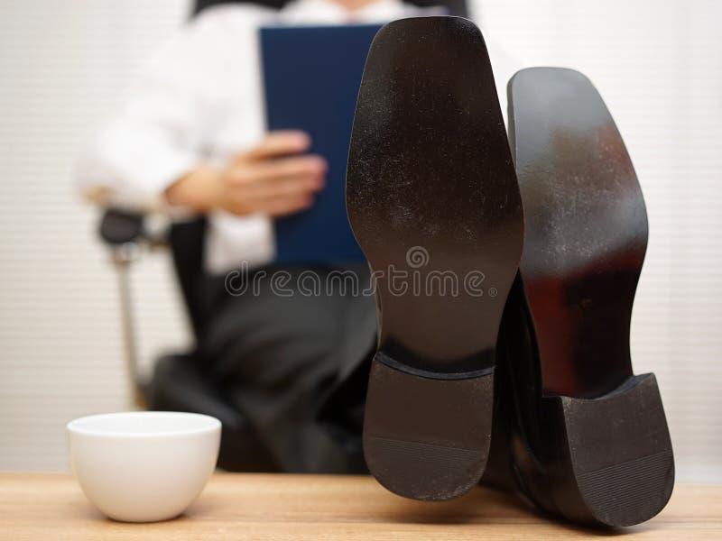 Homem de negócios que senta-se no relatório da leitura da cadeira com seus pés no fotos de stock