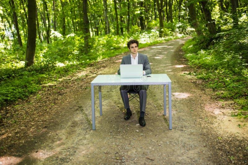 Homem de negócios que senta-se no trabalho de mesa do escritório no laptop em Forest Park verde Freelancer que trabalha na tabela fotos de stock royalty free