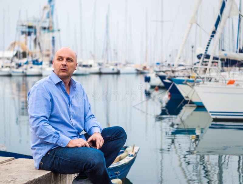 Homem de negócios que senta-se por barcos e por iate caros de navigação na A.A. foto de stock royalty free