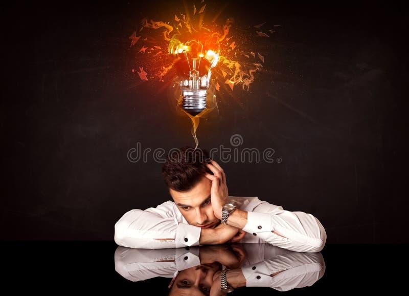 Homem de negócios que senta-se sob um bulbo de sopro da ideia fotografia de stock