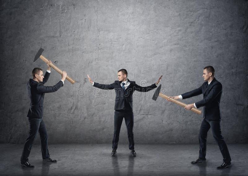 Homem de negócios que separa dois homens de negócios de combate com martelos imagem de stock royalty free