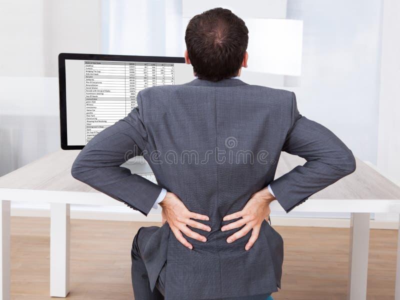 Homem de negócios que sofre da dor lombar ao sentar-se na mesa imagem de stock royalty free