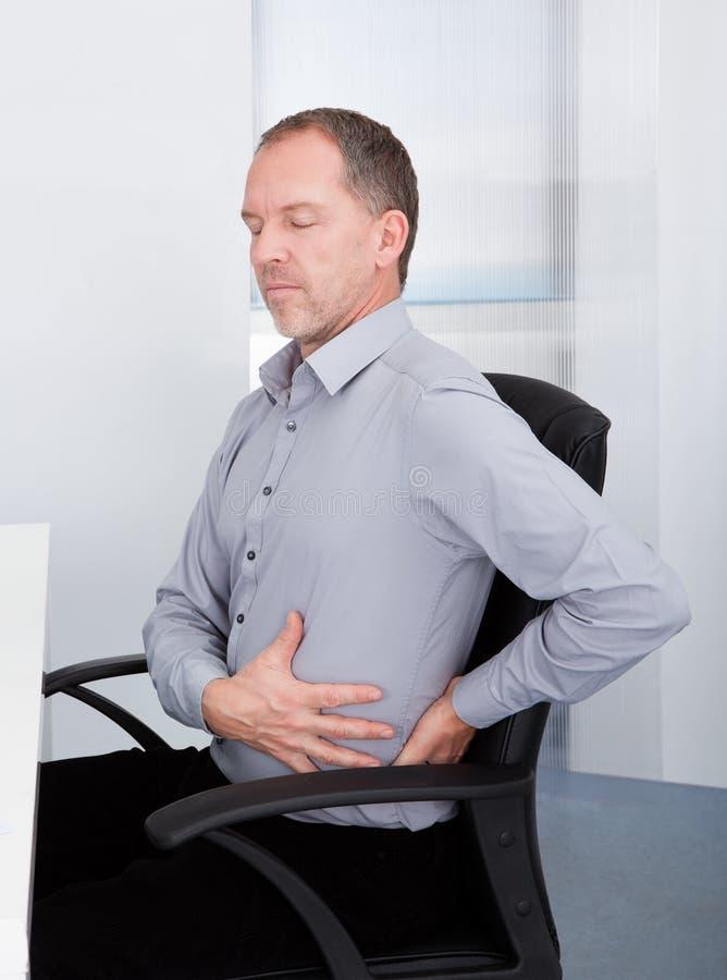 Homem de negócios que sofre da dor nas costas imagem de stock