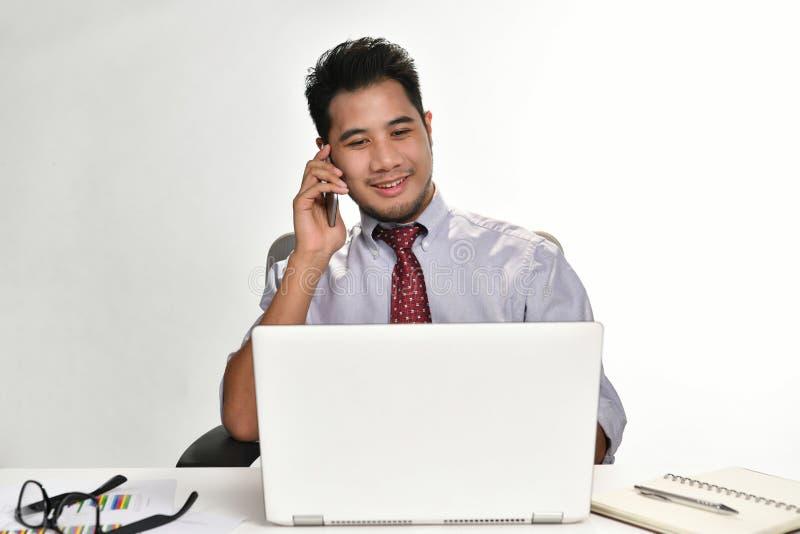 Homem de negócios que sorri ao falar no telefone e ao trabalhar com laptop imagens de stock royalty free