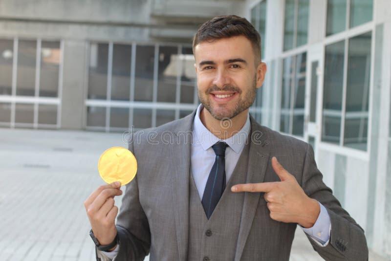 Homem de negócios que sorri ao guardar um Bitcoin imagens de stock