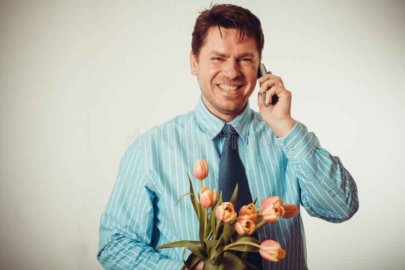 Homem de negócios que sorri ao telefonar e ao guardar a tulipas fotos de stock royalty free
