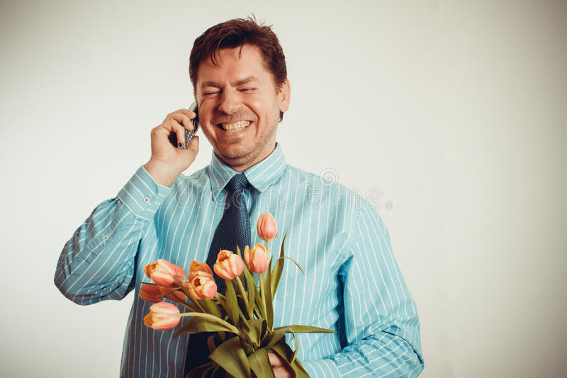 Homem de negócios que sorri ao telefonar e ao guardar a tulipas fotografia de stock