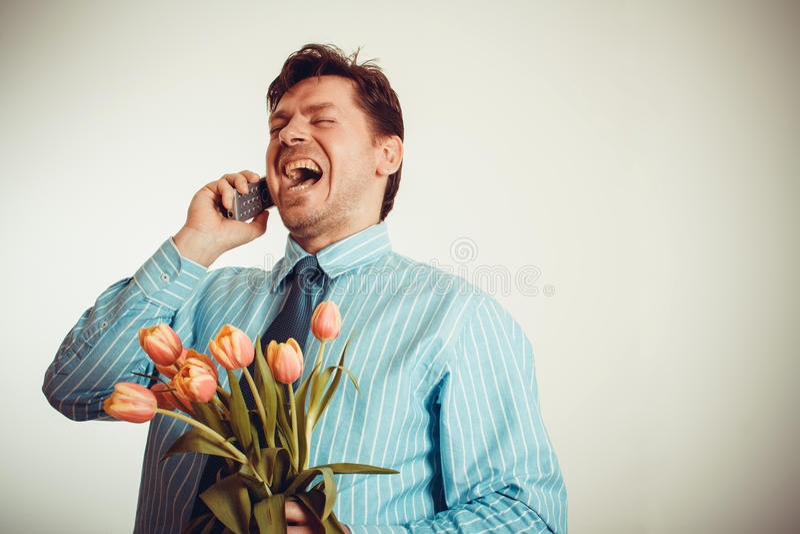 Homem de negócios que sorri ao telefonar e ao guardar a tulipas imagem de stock