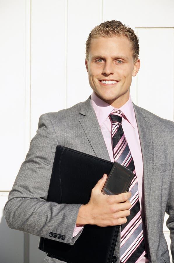 Homem de negócios que sorri com dobrador fotos de stock