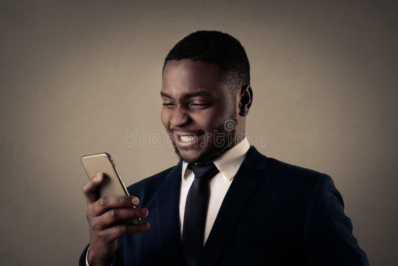 Homem de negócios que sorri e com seu telefone fotografia de stock
