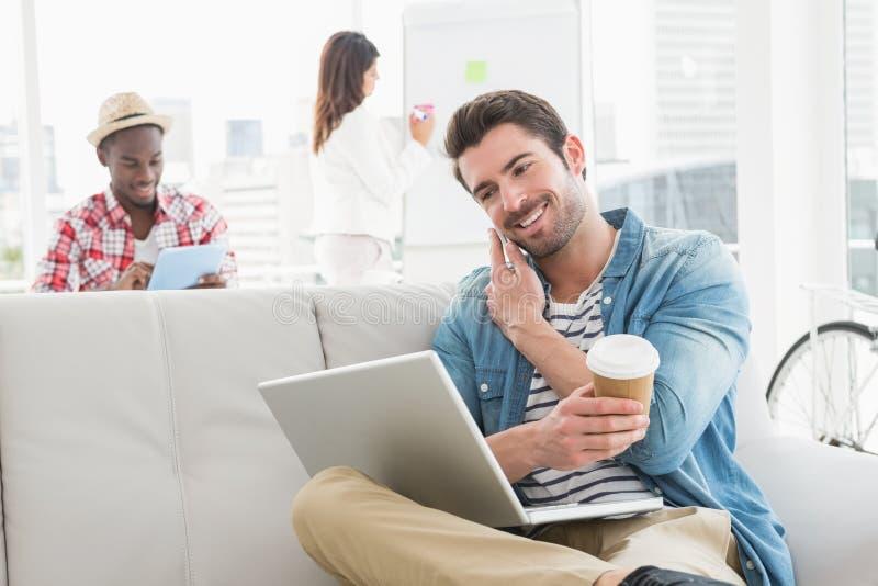 Homem de negócios que telefona e que guarda ao portátil no sofá foto de stock royalty free