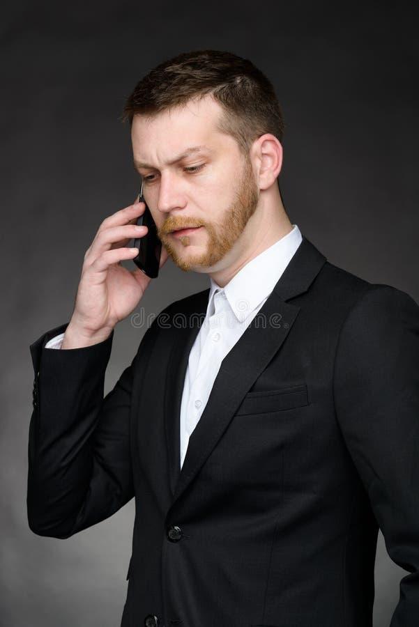 Homem de negócios que tem a conversação no smartphone imagem de stock royalty free