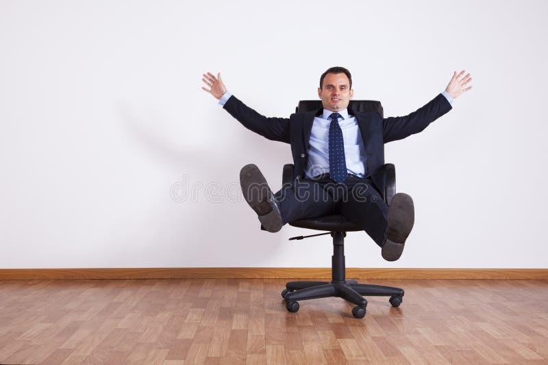 Homem de negócios que tem o divertimento com sua cadeira imagens de stock royalty free
