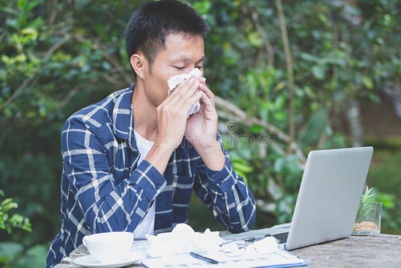 Homem de negócios que tem o frio na cabeça e que senta-se no local de trabalho, H fotos de stock royalty free