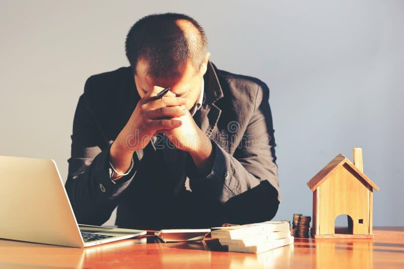 Homem de negócios que tem uma dor de cabeça, cansada e a tensão sobre a propriedade dos bens imobiliários e da posse, sentindo co fotos de stock