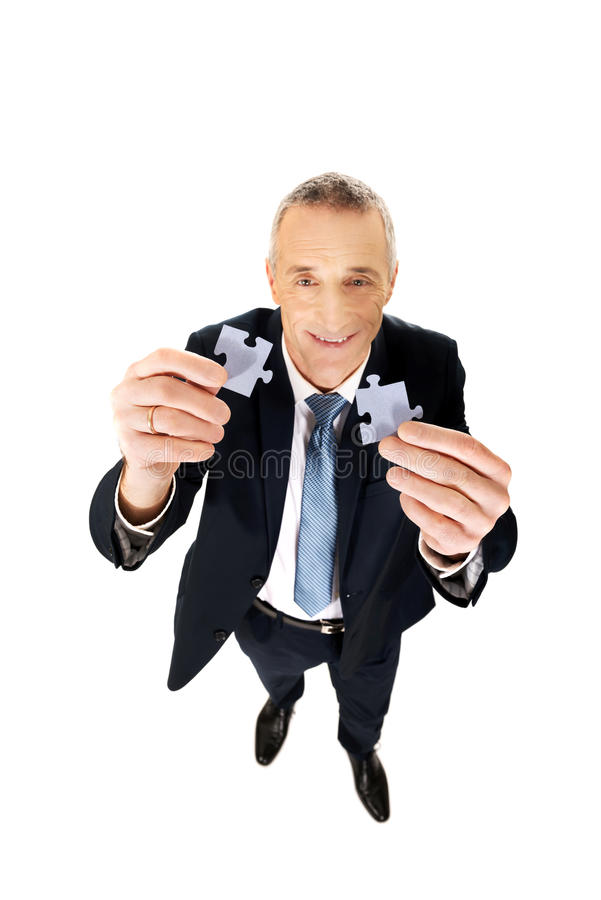 Homem de negócios que tenta conectar partes do enigma imagens de stock royalty free