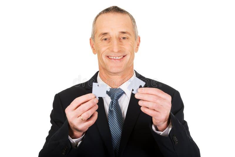Homem de negócios que tenta conectar partes do enigma imagem de stock royalty free