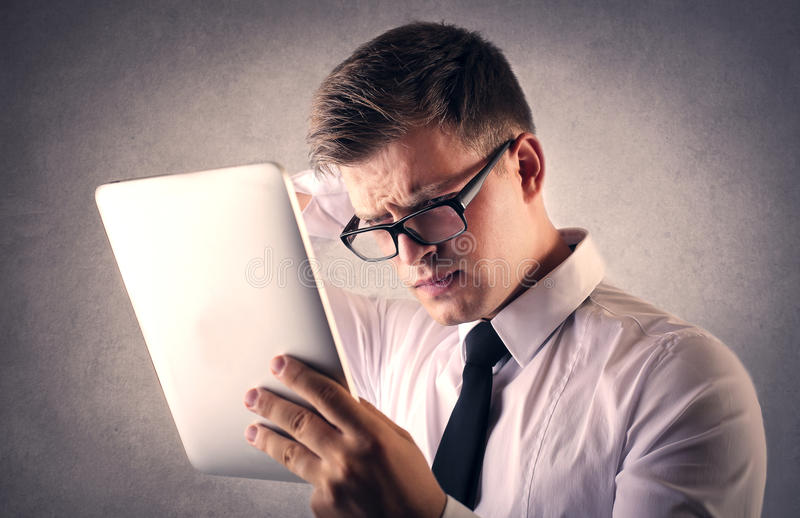 Homem de negócios que tenta ler algo na tabuleta fotografia de stock
