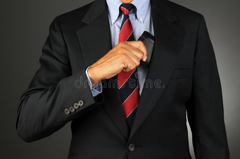 Homem de negócios que toma a carteira do interior do bolso do revestimento imagem de stock