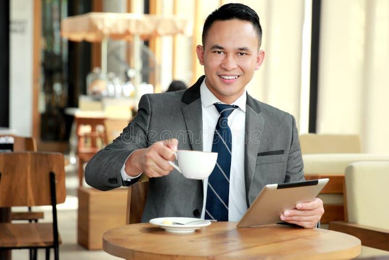 Homem de negócios que toma uma ruptura na cafetaria fotografia de stock royalty free