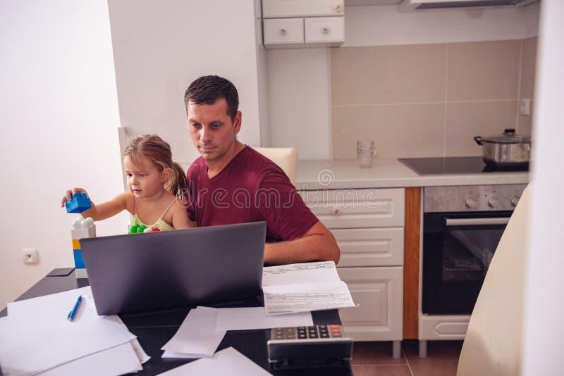 Homem de negócios que trabalha com computador ao ocupar de seu daught imagem de stock