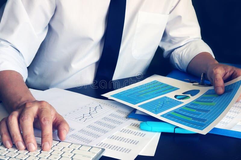 Homem de negócios que trabalha com computador e originais de negócio financeiros foto de stock