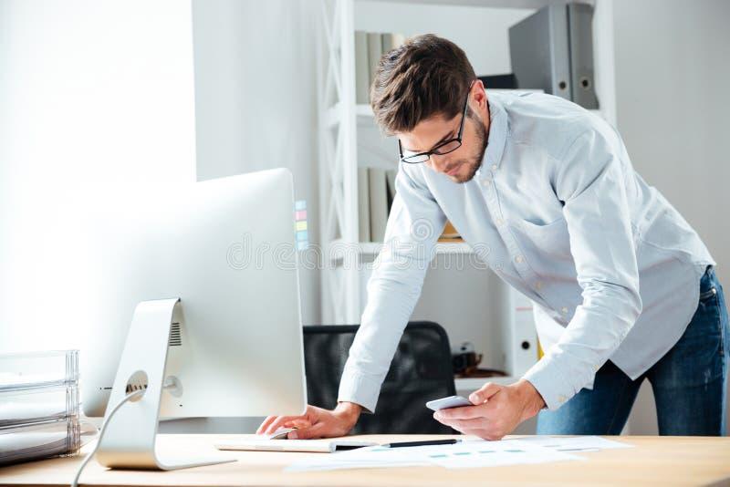 Homem de negócios que trabalha com computador e que usa o telefone celular no escritório imagens de stock royalty free