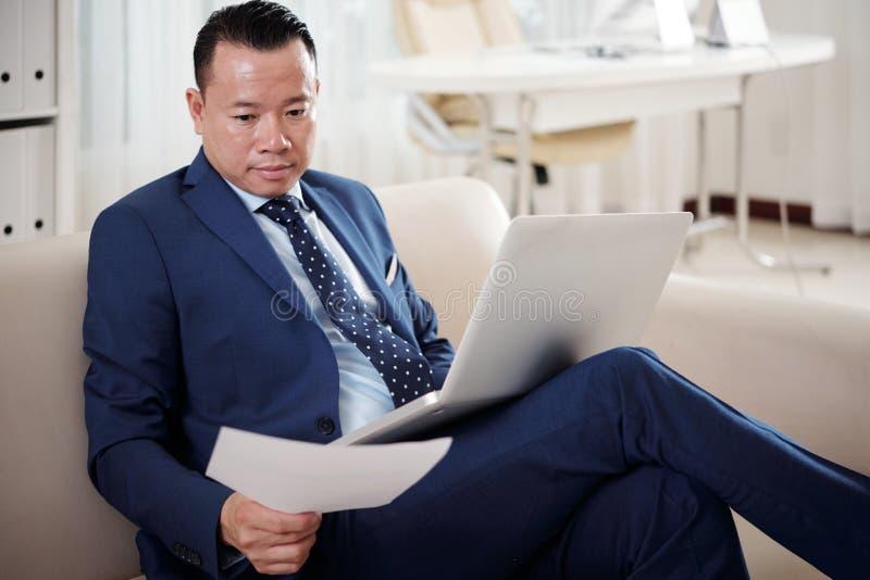 Homem de negócios que trabalha com contrato e portátil no escritório imagem de stock