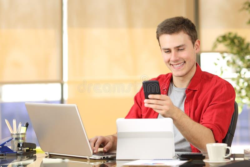 Homem de negócios que trabalha com dispositivos múltiplos foto de stock