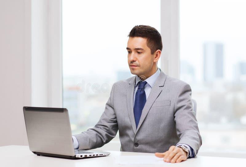 Homem de negócios que trabalha com o portátil no escritório foto de stock royalty free