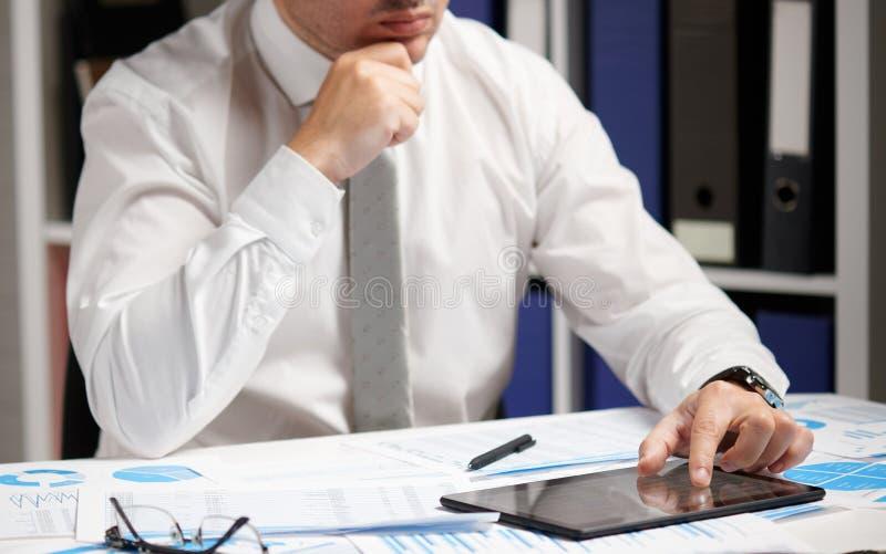 Homem de negócios que trabalha com PC da tabuleta, calculando, lendo e escrevendo relatórios Empregado de escritório, close up da imagem de stock