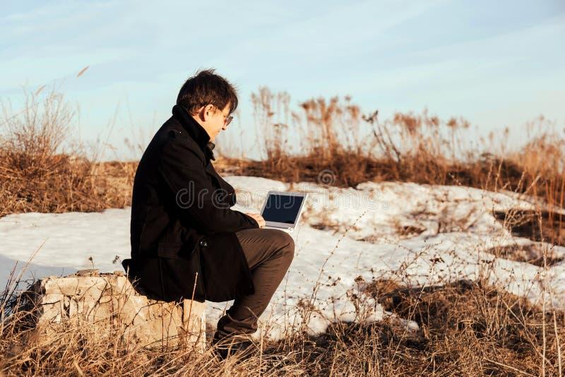 Homem de negócios que trabalha com seu portátil fora imagem de stock royalty free