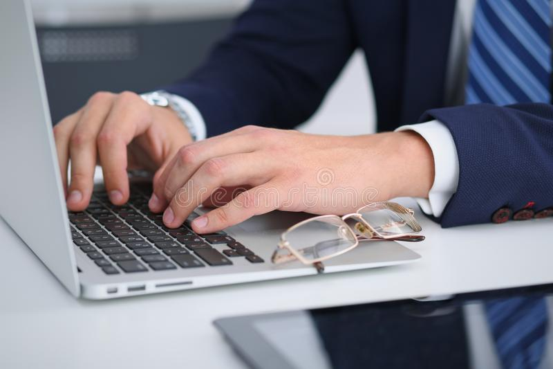 Homem de negócios que trabalha datilografando no laptop Equipe as mãos do ` s no caderno ou na pessoa do negócio no local de trab imagens de stock
