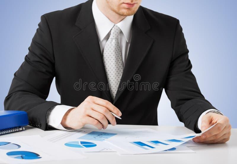Homem de negócios que trabalha e que assina com papéis foto de stock