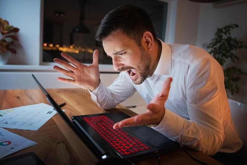 Homem de negócios que trabalha em um portátil, sobrecarregando, sob a pressão fotos de stock royalty free