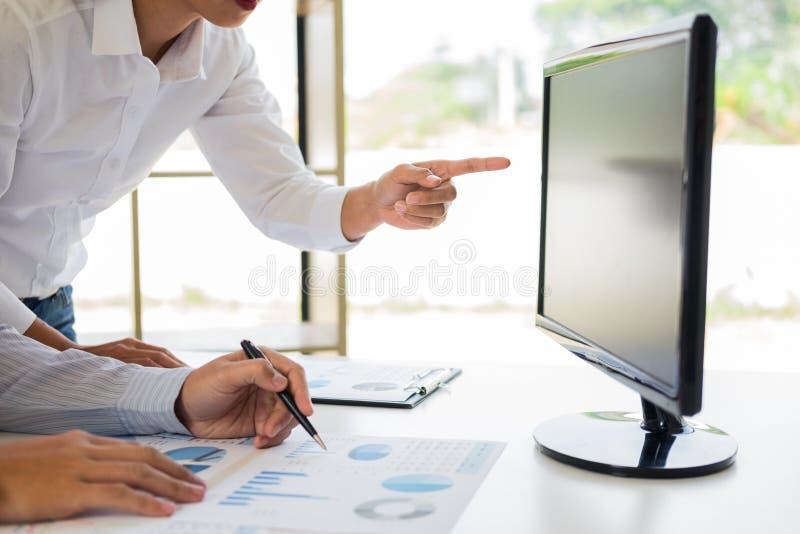 Homem de negócios que trabalha junto apontando a tela ao discutir explicando uma análise de negócio indicada no computador de sec fotos de stock royalty free