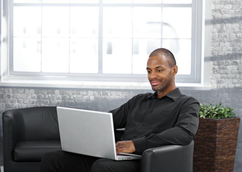 Homem de negócios que trabalha na poltrona foto de stock