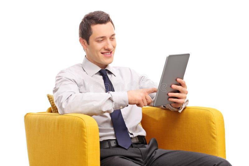 Homem de negócios que trabalha na tabuleta assentada em uma poltrona imagem de stock