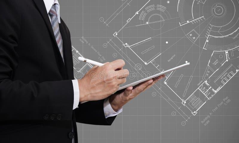 Homem de negócios que trabalha na tabuleta digital com fundo arquitetónico do desenho do plano do modelo, arquiteto, concep do ne imagens de stock royalty free