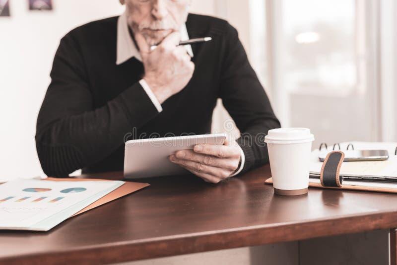 Homem de negócios que trabalha na tabuleta digital no escritório foto de stock royalty free