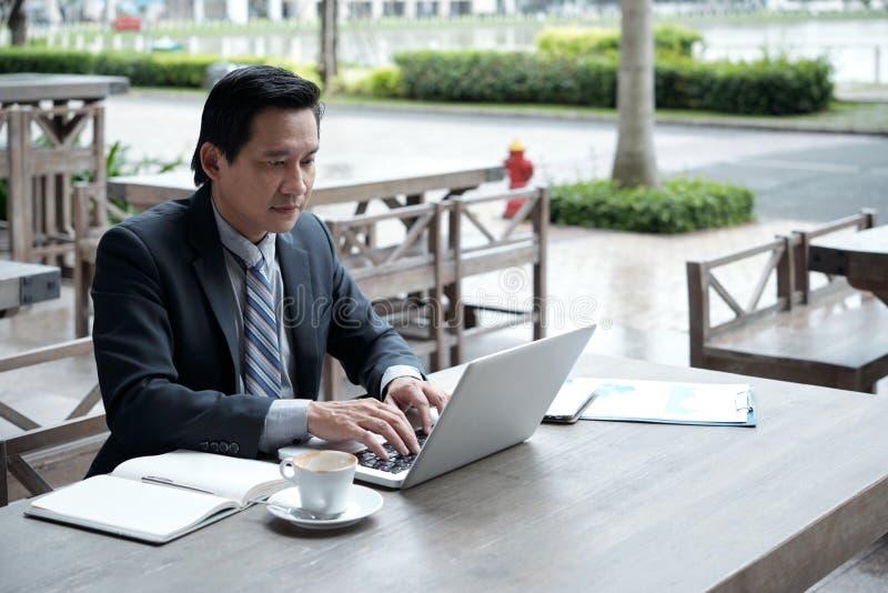 Homem de negócios que trabalha no café exterior fotos de stock royalty free
