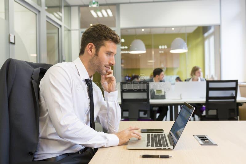 Homem de negócios que trabalha no computador no escritório moderno fotografia de stock royalty free