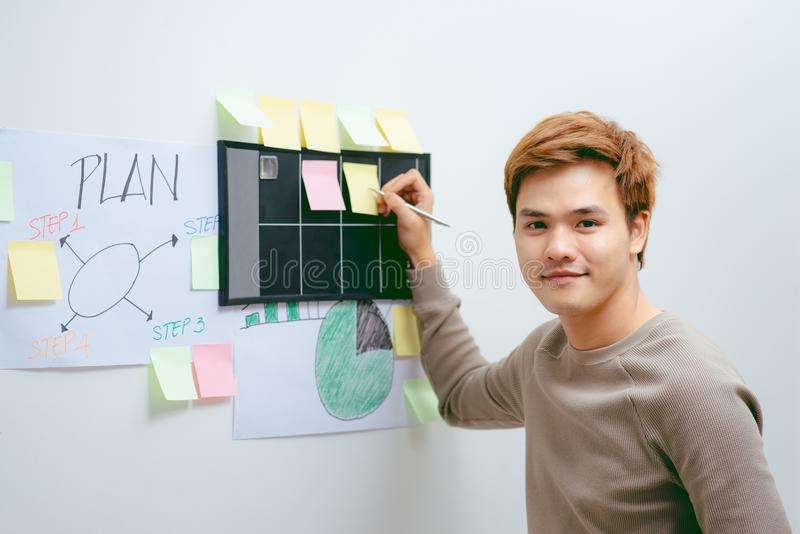 Homem de negócios que trabalha no escritório com as pilhas dos livros e dos papéis fotos de stock