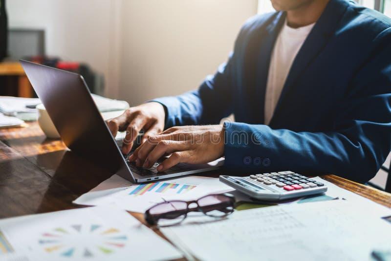 homem de negócios que trabalha no escritório da mesa com utilização do portátil do computador, conceito de contabilidade da finan fotos de stock