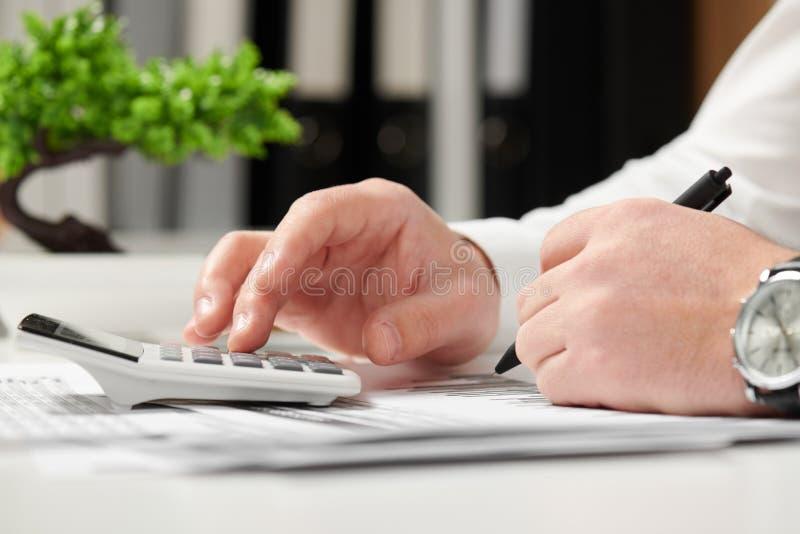 Homem de negócios que trabalha no escritório e que calcula a finança conceito de contabilidade financeira do negócio imagem de stock