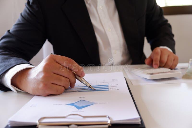 Homem de negócios que trabalha no escritório usando a calculadora com documento na mesa fotos de stock