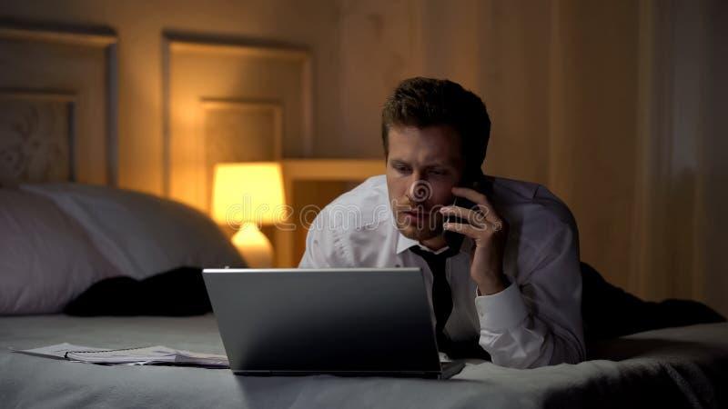 Homem de negócios que trabalha no portátil e que fala no smartphone com o sócio, consultando fotos de stock