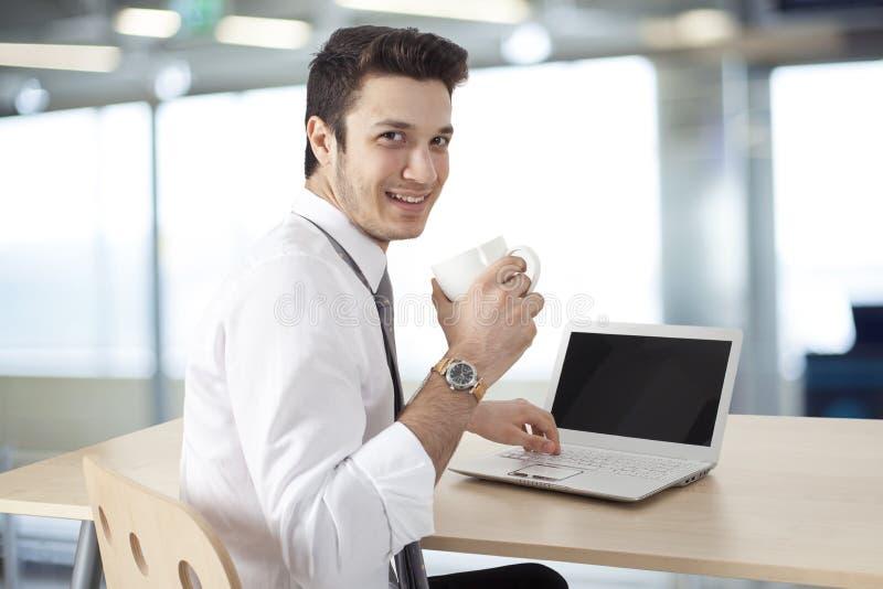 Homem de negócios que trabalha no portátil e no café da bebida foto de stock royalty free