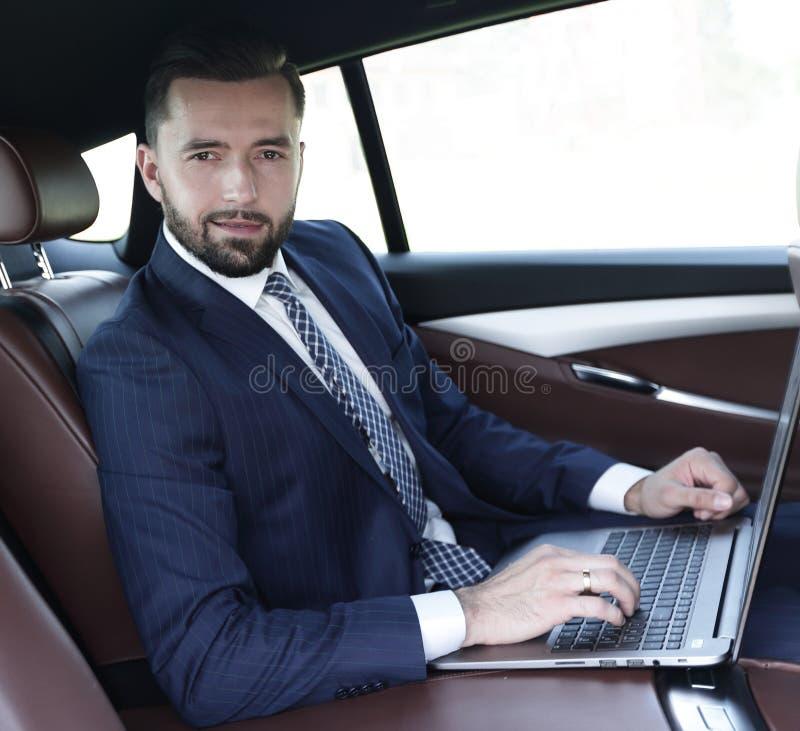 Homem de negócios que trabalha no teclado do portátil que senta-se no carro foto de stock